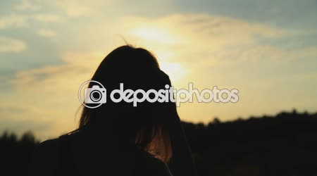 A silhouette of a woman  on a sunset touching her hair