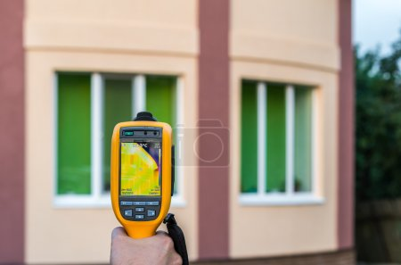 Man inspects house with thermal imaging camera