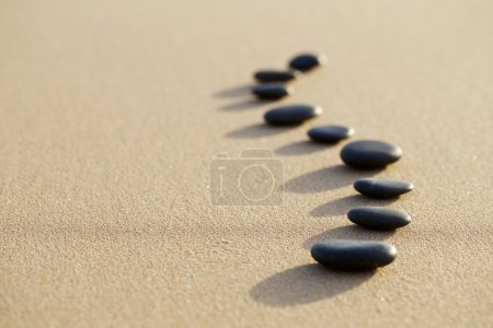 Photo pour Ensemble de pierres chaudes sur la plage calme de sable blanc en forme de colonne vertébrale. mise au point sélective, concept spa - image libre de droit