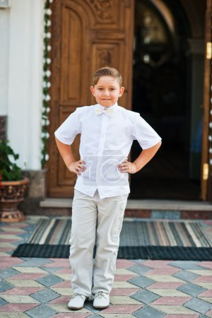 Portrait of little boy on white wear and bow tie on first holy c