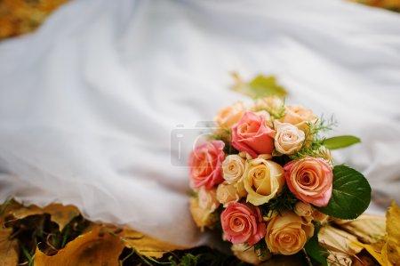 wedding bouquet background wedding dress in yellow autumn leaves