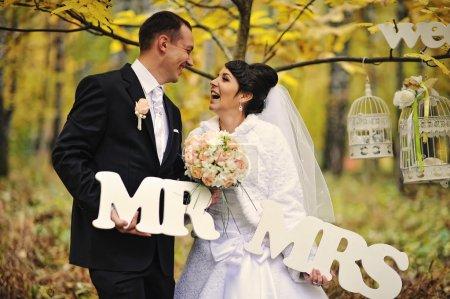 Joyeux couple de mariage en journée d'automne avec signe Mme et M.