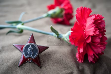 Photo pour Order of the Red Star and two red carnations. Still life dedicated to Victory Day. 9 May - image libre de droit