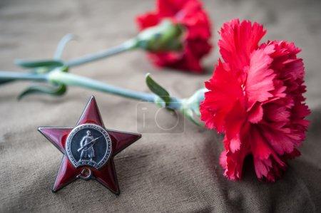 Photo pour Ordre de l'Étoile Rouge et deux œillets rouges. Nature morte dédiée au Jour de la Victoire. Le 9 mai - image libre de droit