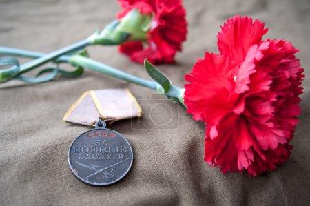 Photo pour Médaille soviétique pour le service de combat et deux oeillets rouges. Nature morte dédiée au Jour de la Victoire. Le 9 mai. - image libre de droit