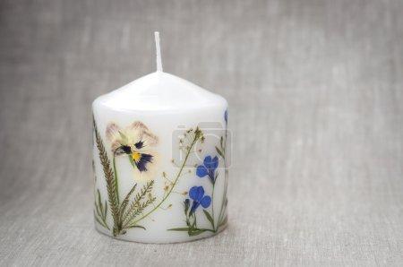 Photo pour Bougie avec des fleurs d'herbier sur le tissu de lin - image libre de droit