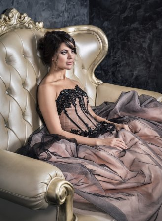 A girl sits in a ball gown dress.