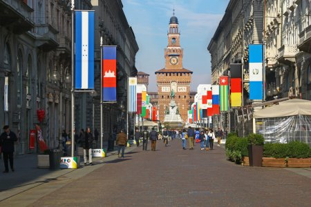 Photo for Milan, Italy. Via Dante with Castello Sforzesco visible at the end. Many people have a walk in the sunny day of late winter. Many flags are set along the street, to remind that this year Milan will host Expo 2015 from 1st of May to 31st of October. - Royalty Free Image