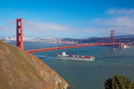 Foto de SAN FRANCISCO, CALIFORNIA - 21, AUGUST 2013: Golden Gate & cargo ship passing below on , August 2013 in San Francisco, USA - Imagen libre de derechos