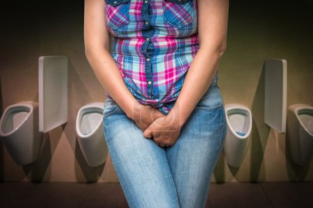 Woman with hands holding her crotch on men's public toilet