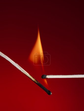 Photo for Macro shot of a flaming matchstick on a red background - Royalty Free Image