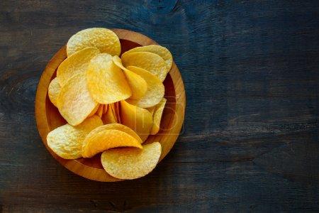Crispy potato chips in bowl on wooden background, ...
