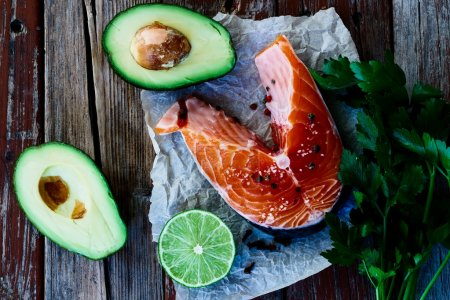Top view of fresh salmon steak, avocado, lime and ...