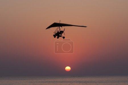 Photo pour La personne à voler sur un parapente avec le moteur contre une baisse. - image libre de droit