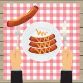 Hand with a knife and sausages on a plate