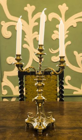 Gold candlestick with candles on the table