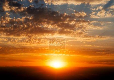 Photo pour Beau ciel nuageux bleu avec coucher de soleil rouge doré et rayons de lumière - image libre de droit