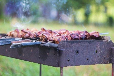 Photo pour Processus de cuisson de la viande sur le barbecue, en gros plan en forêt avec de l'herbe - image libre de droit