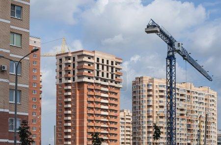 Photo pour Grue de construction sur fond de panorama de bâtiments résidentiels neufs - image libre de droit