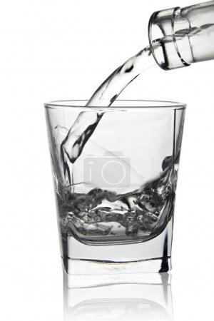 Water pouring into glass, close-up view, isolated on white
