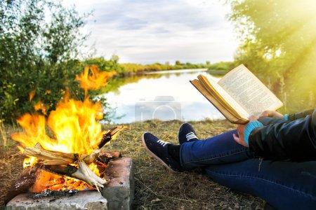 Photo pour Jeune fille tenant un café chaud et lisant un livre près du feu de joie sur le fond d'un lac pittoresque - image libre de droit
