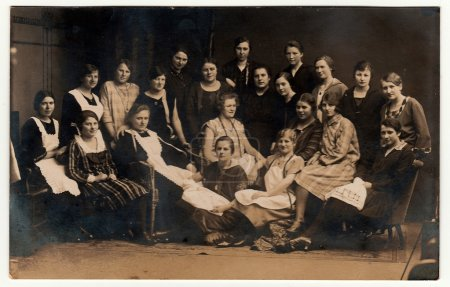 Vintage photo shows young girls (schoolmates, students). Black & white antique photography.