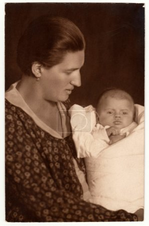 Vintage photo shows woman with baby (newborn) in swaddling clothes. Retro black & white studio photography.