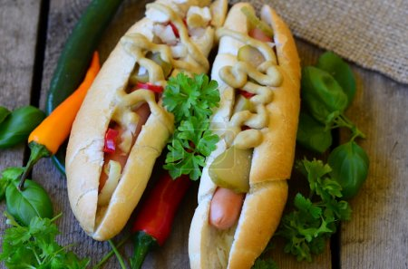 Hot dog with chilli, sport peppers, onion and cucumbers on white plate with wood background