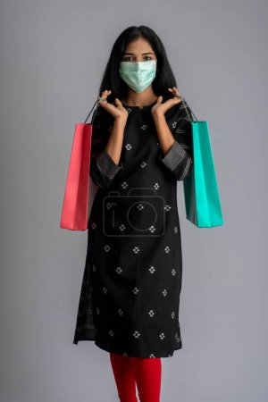 Young woman girl wearing medical mask holding shop...