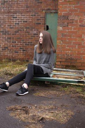Photo pour Jolie jeune adolescente assise sur de vieilles portes devant un immeuble abandonné - image libre de droit
