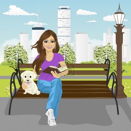 Young happy woman enjoying freetime in city park in summer reading book sitting on a bench hugging labrador puppy