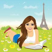 žena leží na trávě, čtení knihy