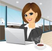 businesswoman working at laptop at airport