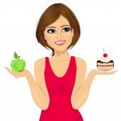 Closeup portrait of attractive woman choosing between green apple or sweet piece of cake Diet concept