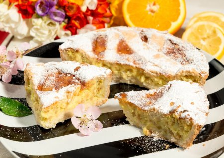 A piece of Neapolitan Easter pie sprinkled with icing sugar and decorated with almond blossom,freesia and fresh fruits.