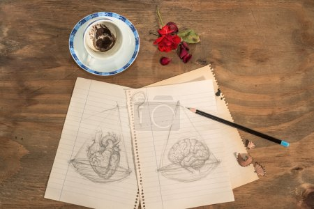 Photo for Empty cup with coffee grounds into a heart shape , dried rose petals , pencil and drawing of a balance with heart and brain . - Royalty Free Image