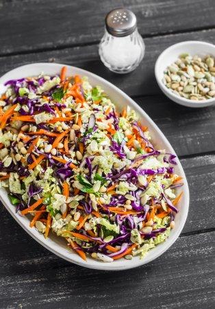 Photo pour Salade de chou aux graines et aux pignons de pin - délicieux plats végétariens sains. Sur un fond de bois rustique foncé - image libre de droit