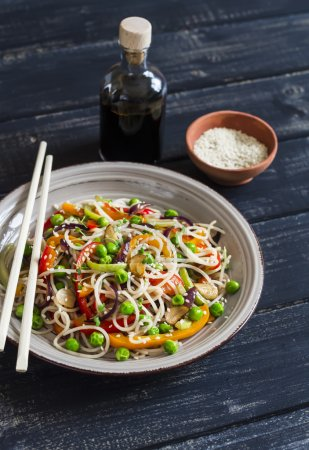 Rice noodles with vegetable stir fry on the ceramic plate on dark wooden background