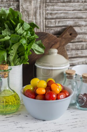 Photo for Fresh tomatoes in a ceramic bowl, green garden herb, olive oil and spices on a light rustic wood background. Kitchen still life - Royalty Free Image