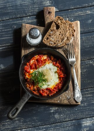 Shakshouka eggs in vintage pan on rustic wooden cutting board on a dark background. Healthy delicious breakfast or snack