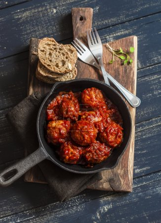 Meatballs in tomato sauce in a cast iron skillet on a wooden rustic board on a dark background