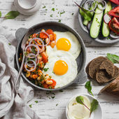 Delicious  breakfast or snack - a fried egg, beans in tomato sauce with onions and carrots, fresh cucumbers and tomatoes, homemade rye bread on light wooden background