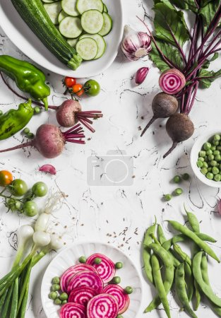 Fresh raw vegetables - beets, green peas and beans, zucchini, peppers, onions, garlic on a light background. Free space for text. Top view