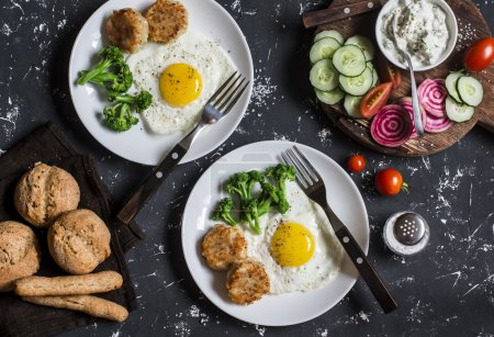 Fried eggs, chicken meatballs, vegetables, and yogurt sauce on a dark background. Healthy lunch or snack