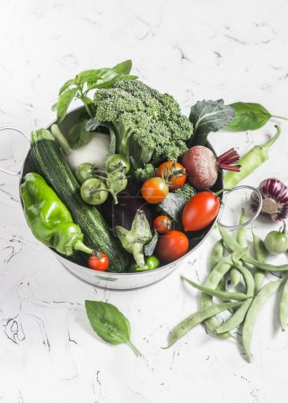 Fresh vegetables - broccoli, zucchini, beets, peppers, tomatoes, green beans, garlic, basil in a metal basket on a light background. Healthy food