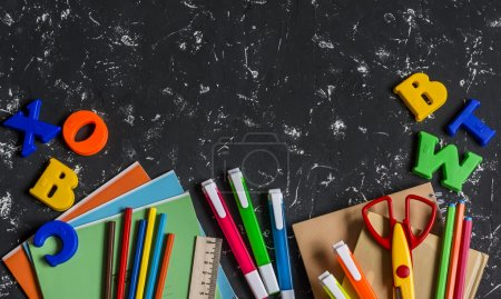 School accessories, stationery on dark background. Top view, free space for text. Concept of education and training