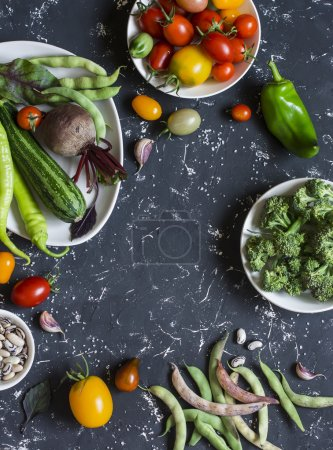 Food background. Assortment of fresh vegetables on a dark background. Top view, free space for text