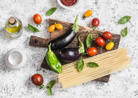 Cooking background. Raw ingredients for making pasta - spaghetti, eggplant, tomatoes, pepper, olive oil, tomato sauce and basil on a rustic cutting board. Top view