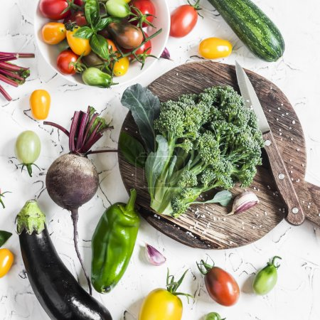 Fresh vegetables - broccoli on rustic cutting board, tomatoes, eggplant, zucchini, beets, peppers, basil on a light background, top view.