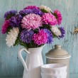 Flowers asters in a white enameled pitcher and vin...